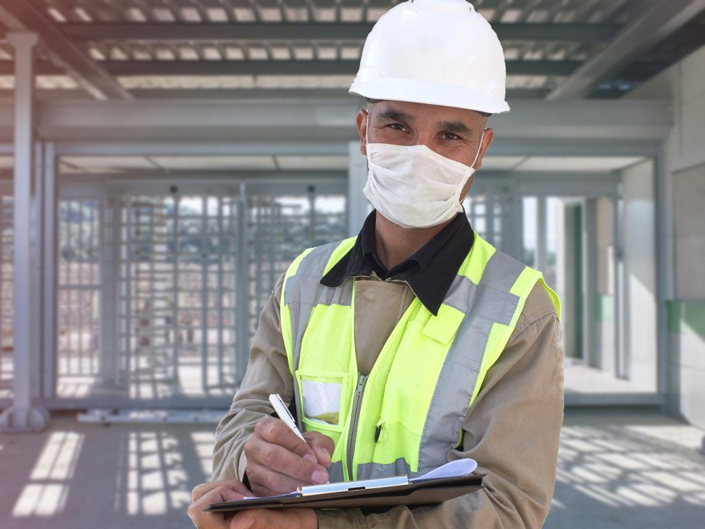 Construction worker in white hardhat and protective mask stands with clipboard opposite checkpoint with turnstile at background